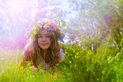 Ung flicka med en blom- krans på hennes huvud på gräset fotografering för bildbyråer