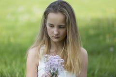 Ung flicka med en grupp av blommor Royaltyfri Bild