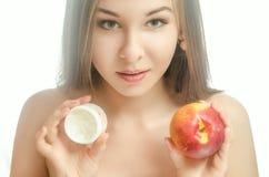 Ung flicka med en persika och en kräm Royaltyfria Foton