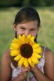Ung flicka med en solros Arkivfoto