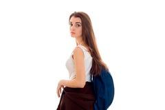 Ung flicka med en stor portfölj på tillbaka värt vända från sidan till kameran som isoleras på vit bakgrund Arkivfoto