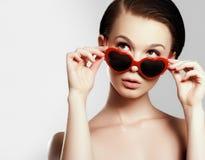 Ung flicka med exponeringsglas i formen av hjärta Falska ögonfrans i form av fjärilar Arkivbild