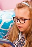 Ung flicka med exponeringsglas som läser i säng Arkivbild