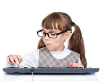 Ung flicka med exponeringsglas som skriver tangentbordet Isolerat på vit backg arkivfoto
