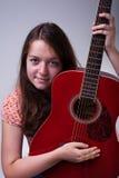 Ung flicka med gitarrståenden Royaltyfri Bild