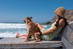 Ung flicka med hennes hund som håller ögonen på havet arkivbild