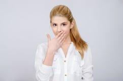 Ung flicka med händer på henne mun som ser förbluffad. Arkivfoton