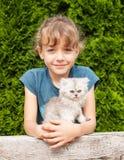 Ung flicka med kattungen av den persiska katten Royaltyfri Bild