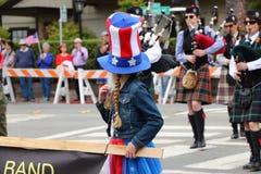 Ung flicka med långa flätade trådar som bär 4th av den Juli hatten Arkivbild