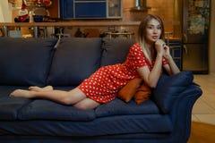Ung flicka med långt hår i en klänning i röda prickar som poserar att ligga på en blå soffa hemma royaltyfria bilder