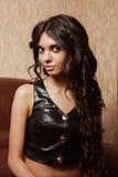 Ung flicka med långt svart hår i attraktiv kvinna för läderväst A en mycket med stora ögon Royaltyfri Foto