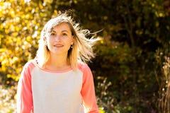 Ung flicka med löst hår på bakgrunden av höstträd arkivbild