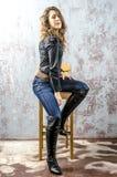 Ung flicka med lockigt hår i en svart skjorta, en jeans och en västra stil för hög kängacowboy Arkivfoto