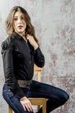 Ung flicka med lockigt hår i en svart skjorta, en jeans och en västra stil för hög kängacowboy Arkivbild