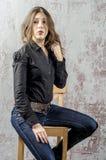 Ung flicka med lockigt hår i en svart skjorta, en jeans och en västra stil för hög kängacowboy Royaltyfria Foton