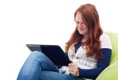 Ung flicka med minnestavladatoren Arkivfoton