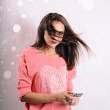Ung flicka med mobiltelefonen på abstrakt bakgrund Royaltyfria Bilder