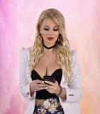 Ung flicka med mobiltelefonen på abstrakt bakgrund Fotografering för Bildbyråer
