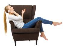 Ung flicka med mobiltelefonen på stol royaltyfri foto