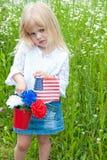 Ung flicka med nejlikor och flaggan arkivbild