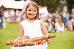 Ung flicka med nytt bröd som köps på den utomhus- bondemarknaden Royaltyfria Bilder