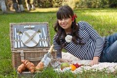 Ung flicka med picknickkorgen i parkera Royaltyfri Foto