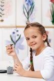 Ung flicka med plantan för studie i biologigrupp Arkivbild