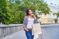Ung flicka med shoppingpåsar, når att ha shoppat i staden Arkivbilder