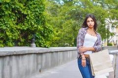 Ung flicka med shoppingpåsar, når att ha shoppat i staden Royaltyfri Foto