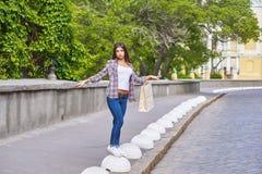 Ung flicka med shoppingpåsar, når att ha shoppat i staden Royaltyfria Bilder