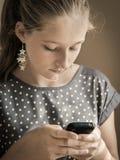 Ung flicka med smartphonen Royaltyfria Foton
