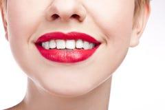 Ung flicka med snow-white leende. Röd läppstift Fotografering för Bildbyråer