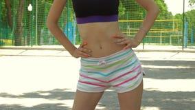 Ung flicka med spenslig buckla i kortslutningar som gör övningar på gatorna lager videofilmer