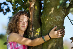 Ung flicka med stängda ögon omfamna trädet Arkivbild