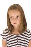 Ung flicka med stora ögon som biter hennes kant Arkivbild