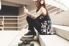 Ung flicka med tatueringen och dreadlocks som lyssnar till musik, medan sitta på momenten royaltyfria foton