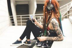 Ung flicka med tatueringen och dreadlocks som lyssnar till musik, medan sitta på momenten arkivbild