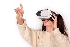 Ung flicka med två hästsvansar i anseende för virtuell verklighethörlurar med mikrofonstudio som isoleras på den imponerade vita  arkivbilder