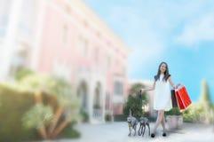 Ung flicka med två vinthundar som rymmer shoppingpåsar Royaltyfria Bilder