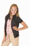 Ung flicka med vita moderiktiga exponeringsglas som ler händer på höfter Fotografering för Bildbyråer