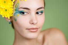 Ung flicka modellerar med fantasimakeup och blommor arkivfoto
