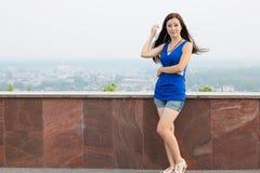 Ung flicka nära väggen, men bakgrunden av staden Arkivfoto
