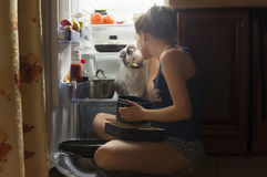 Ung flicka och hennes fluffiga katt som äter på natten Royaltyfri Fotografi