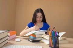 Ung flicka och information om handstil som hon har funnit i en stor bok in i hennes anteckningsbok Royaltyfri Bild