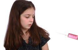 Ung flicka och injektionsspruta Royaltyfria Foton