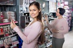 Ung flicka och mogen kvinna som väljer makeupprodukter Arkivbild