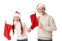 Ung flicka och pojke i santa hattar Royaltyfri Foto