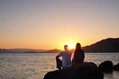 Ung flicka och pojke som sitter på en rock Arkivbild