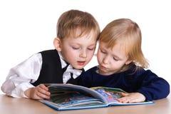 Ung flicka och pojken ser boka royaltyfri bild