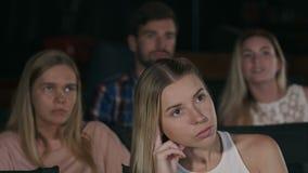 Ung flicka på bion som håller ögonen på en film stock video